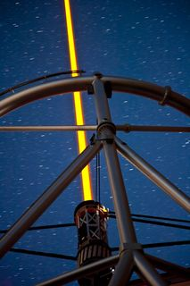 Photo of a steel structure with a yellow laser beam at its centre pointing towards the star-filled sky at night.