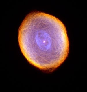 Photo of a luminous dot at the centre of a cloudy blue, purple, pink and orange mass against a very black background