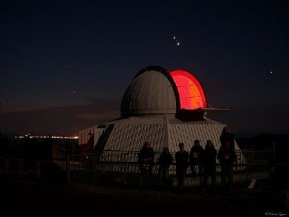Nighttime photo of a white building with its open dome giving off red light and people observing the star-filled sky
