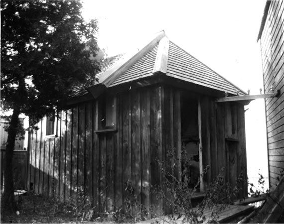 Black and white photo of a small building made of vertically positioned wood planks with a shingle roof, an open door and three small windows