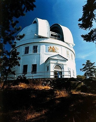 Colour photo of a white building with its dome open located at the top of a wooded hill