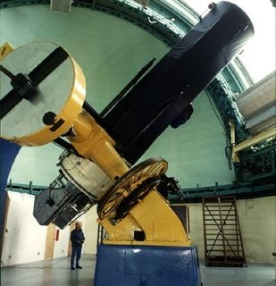Colour photo of a telescope with a blue base, yellow body and black telescopic tube pointing towards the opening of a white dome