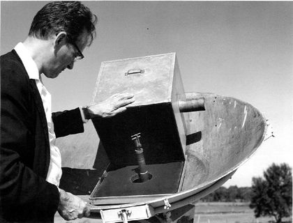 Black and white photo of a man in profile wearing glasses and examining the mechanism of an antenna.