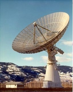 Photo of a fenced-in white parabolic antenna made of metal pointing towards the sky, located to the right of a small white building with snow-covered hills in the background