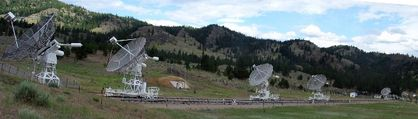 Panoramic photo of five white white antennas pointing towards the sky, located in a field with forested mountains in the background.