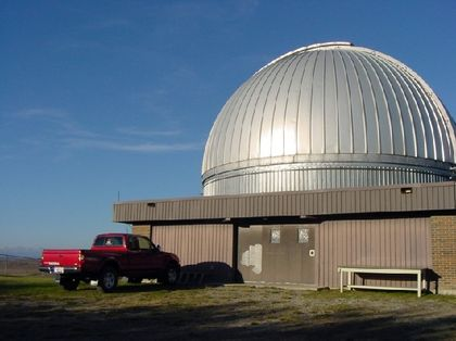 Photo of the exterior of a silver-coloured metal dome and a rectangular building with a red truck parked in front