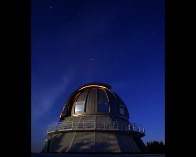 Night photo of a metal dome under a star-filled sky