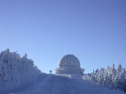 Photo of  a white dome located at the end of a wooded lane covered with a thick layer of white snow, with a blue sky as a backdrop