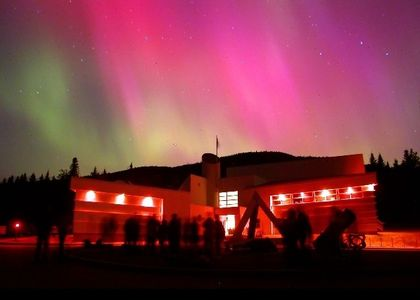 Night photo of a lit building with green and pink-tinged Northern Lights in the background. People are standing in front of the building looking skyward.