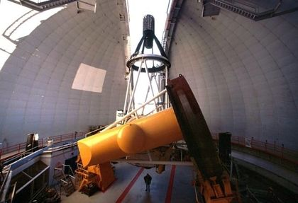 Photo of the structure of a yellow and white telescope pointing towards the sky through an opening in a white dome