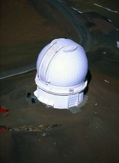 Aerial photo of an observatory with its white dome closed, located on undeveloped land
