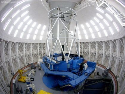 Photo of the interior of an observatory with its dome closed. The walls are white and the base of the telescope is blue.