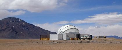 Photo of a white protective dome surrounded by rectangular buildings and a truck, taken in the desert with a grey mountain to the left and a cloudy blue sky as a backdrop.