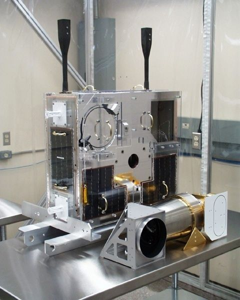 Colour photo of a rectangular telescope made of metal components positioned on a table in a closed room.