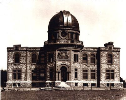 Photo in sepia of of a stone building with a metal dome at its centre