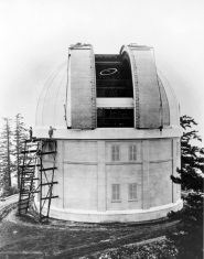 Black and white photo of a cylindrical white building with a white dome that is open and a stairway on the left leading to the side of the dome