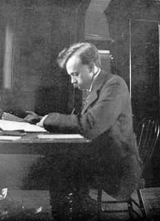 Black and white photo of a man with a mustache seated at a desk, leaning over some papers