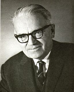 Black and white photo of a man with black-rimmed glasses wearing a suit and tie