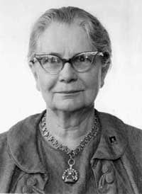 Black and white photo of a woman with glasses and her hair tied back