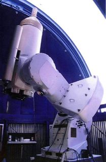 Photo of a telescope in front of a blue dome open to a very white sky