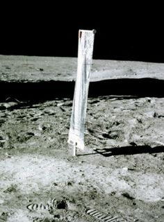 Photo of a vertical strip of cloth installed on the lunar soil behind traces of footprints on the ground with a very black sky in the background