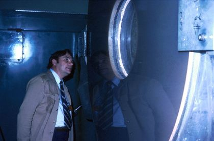 Photo of a man wearing a beige coat and a tie looking through the round window in a metal wall