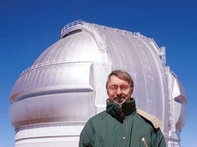 Photo of a man with glasses wearing a green coat in front of a  building with a silver-coloured metal dome