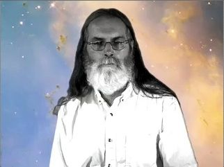 Black and white photo of a man with a beard and long hair wearing glasses against a starry blue and yellow background