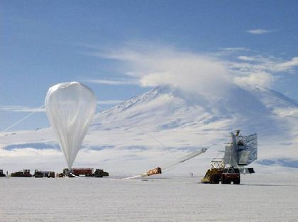 Photo of a balloon attached to a telescope installed on the platform of a truck in the desert, with a high, snow-covered mountain in the background