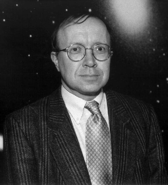 Black and white photo of a man with glasses wearing a suit with a star-filled sky in the background