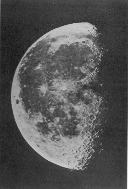 Black and white photo of the left side of a half-moon revealing craters and dark spots