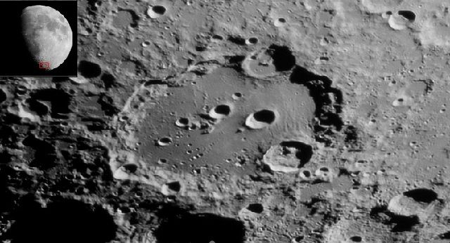 Black and white photo of a lunar crater featuring several small craters and, in an insert, its location boxed in a photo of the moon.
