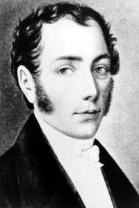 Black and white portrait of a man in profile with long sideburns, looking to his right