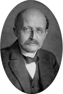 Black and white medallion photo of a man with round glasses and a mustache wearing a bow tie