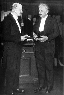 Black and white photo of two men standing, wearing evening dress and having a discussion