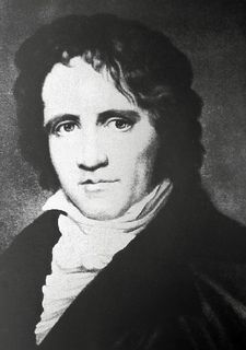 Black and white portrait of a man with curly hair wearing a black jacket and white collar