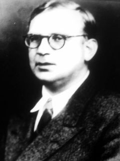 Slightly blurred black and white photo of a man with round glasses wearing a black jacket