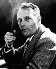 Black and white photo of a man in profile looking at the lens and smoking a pipe