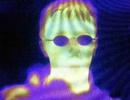 Infrared image of a human head with green, yellowish purple and bluish tinges. The person is wearing glasses easily distinguished on the face owing to their blue colour.