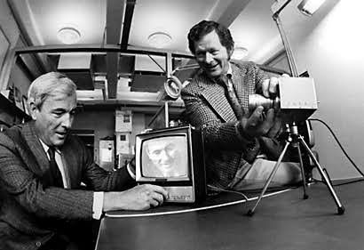 Photo of of a man filming another man using a camera installed on a table and displaying the image directly on a television screen