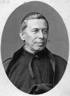 Black and white photo of a man wearing a Jesuit's cassock