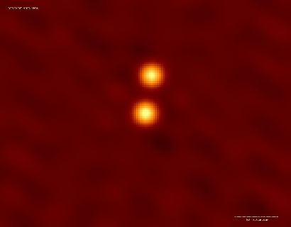 Two superposed orange dots surrounded by a yellowish halo against a red background.