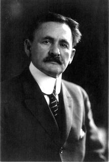 Black and white photo of a man with a mustache wearing a black suit.