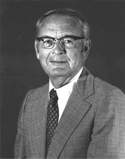 Black and white photo of a man wearing a suit and glasses with black rims.