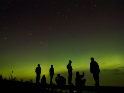Photo of silhouettes of people standing on a hill looking at green Northern Lights in a black sky