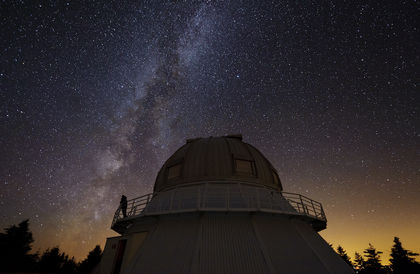 Night photo of a silhouette on the catwalk of an observatory under a star-filled sky at dusk